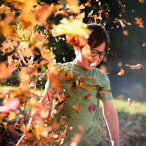 boy playing in fall leaves